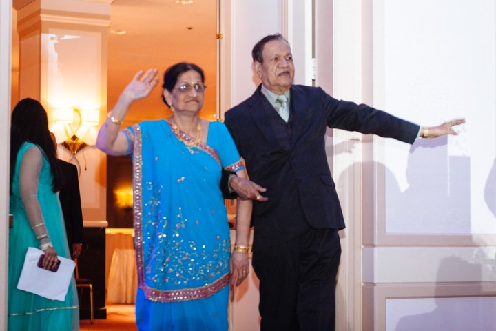 Parents of the bride entering the ballroom for the reception. The mother is wearing a sari with a Gujarati style pallu.