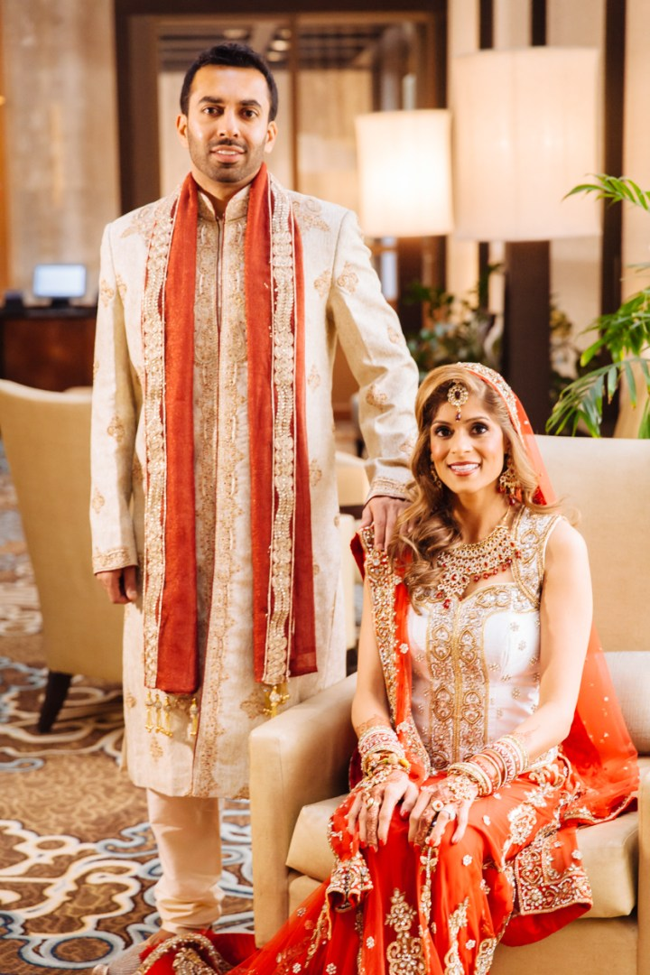 Lovely shot of an Indian bride and groom dressed up for their wedding. The bride wearing a beautiful red and gold lehenga and the groom in a matching sherwani.
