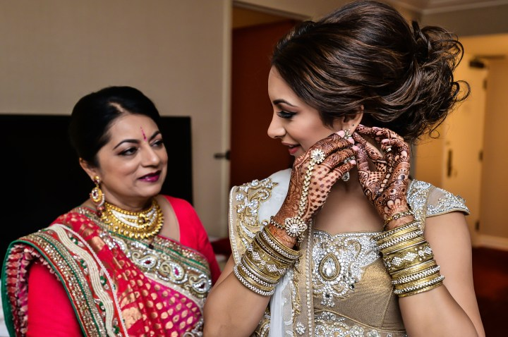 Indian bride putting on her earring while her mom wearing a red sari overlooks