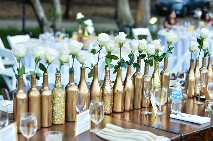 gold painted wine bottles in a row, each with a single white rose lined acrioss rectangular kings tables at an Indian wedding reception.