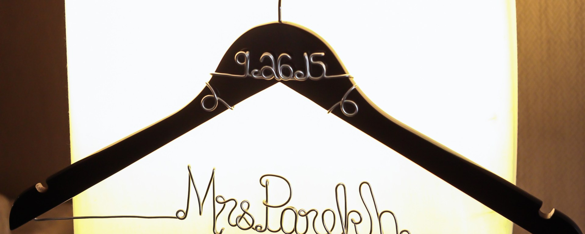 Custom made wire hanger with the bride's new last name ion it.