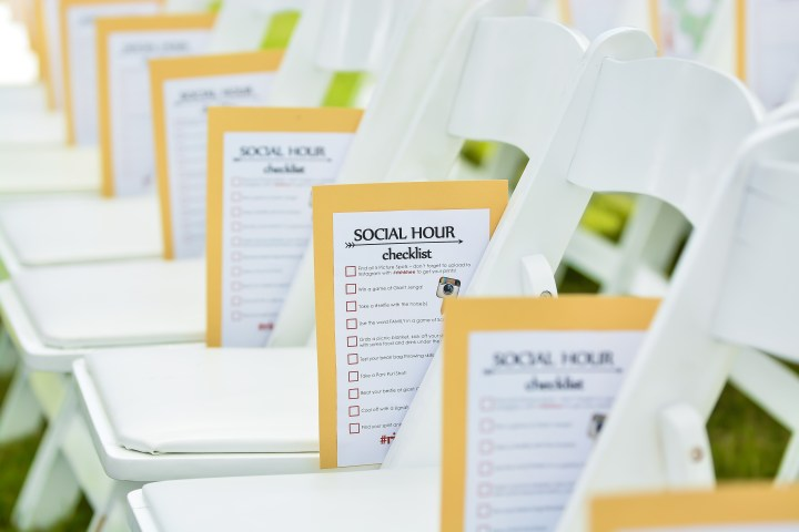 A yellow construction paper with a white sheet of paper o top placed at each chair with suggested activities for guests to do during cocktail hour at an Indian wedding.