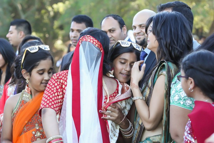 Indian bride hugging her cousins during the vidai after her Hindu wedding ceremony