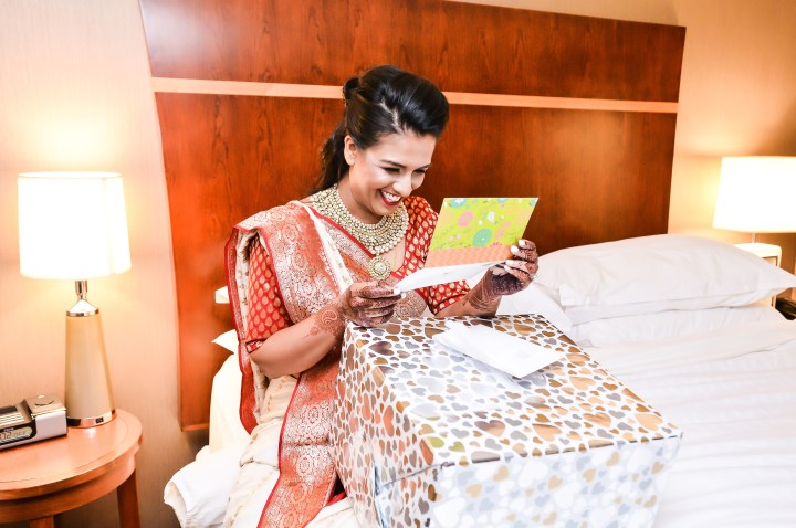 indian bride smiling, reading a card from her husband-to-be