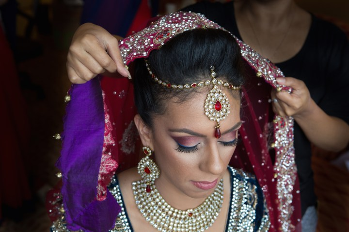 The Indian bride getting her dupatta put onto her head for her Anand Karaj
