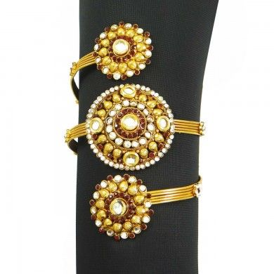 Long gold band wrapping around arm 3 times with bead and diamond details in centre
