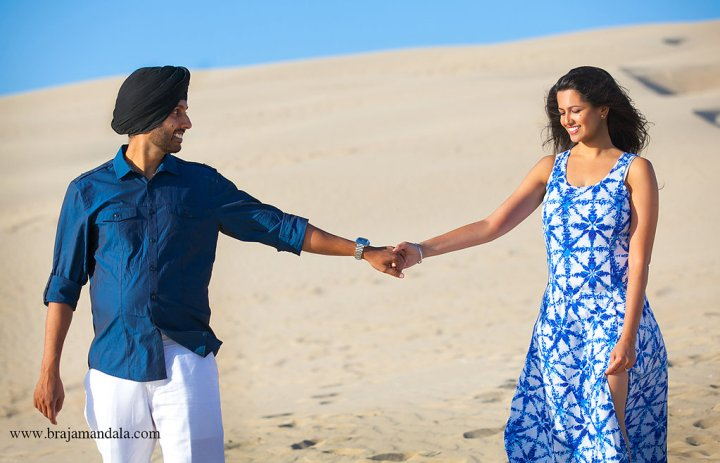 Indian bride and grom holding hands on the beach wearing blue