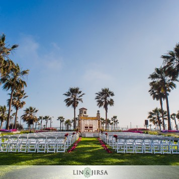 Garden lined with palm trees facing a lighthouse, setup with white garden chairs theater style and a mandap for an Indian wedding ceremony