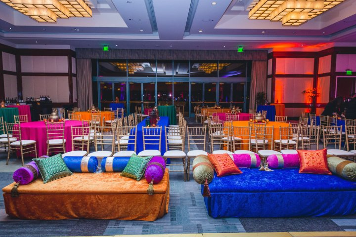 Ballroom decorated in colorful linens and pillows and seating for a sangeet for an Indian wedding.