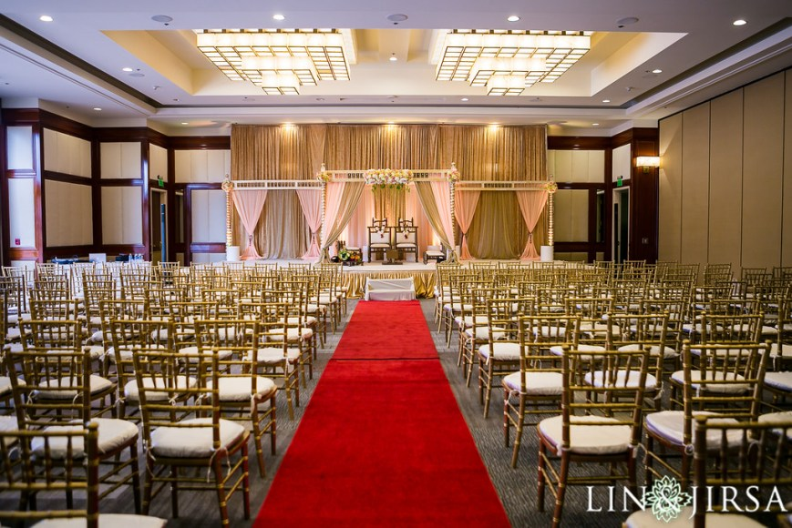 Gold chiavari chairs setup theater style in front of a stage and mandap with a red carpet aisle. This setup is ready for an Indian wedding.