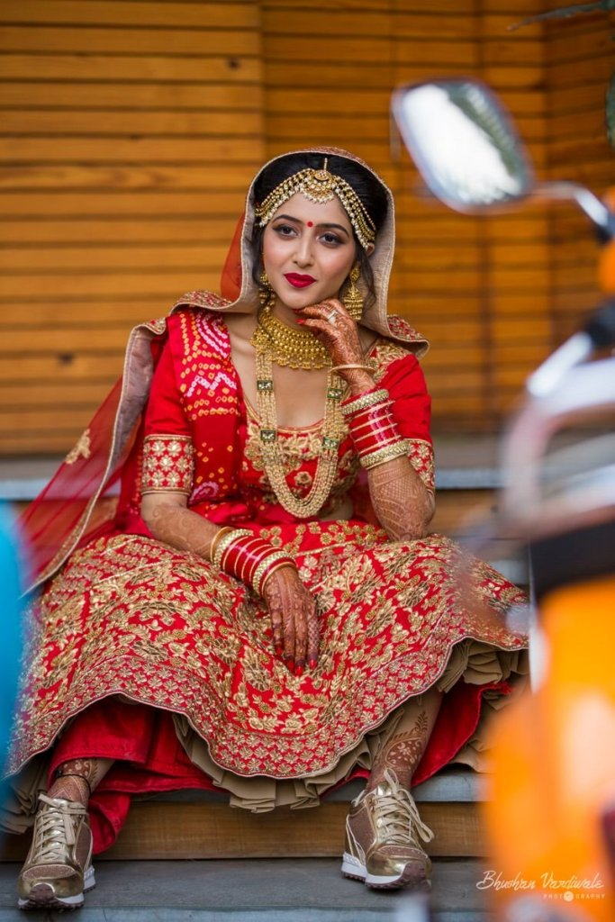 Indian bride in her wedding lehenga wearing sneakers