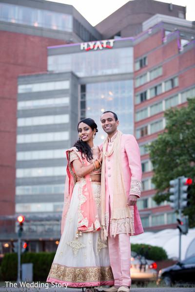 Indian bride and groom standing in wedding attire outside of the Hyatt Regency Cambridge