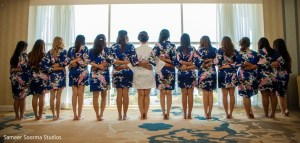 Bride and her bridesmaids wearing matching robes for the photo session on her wedding day