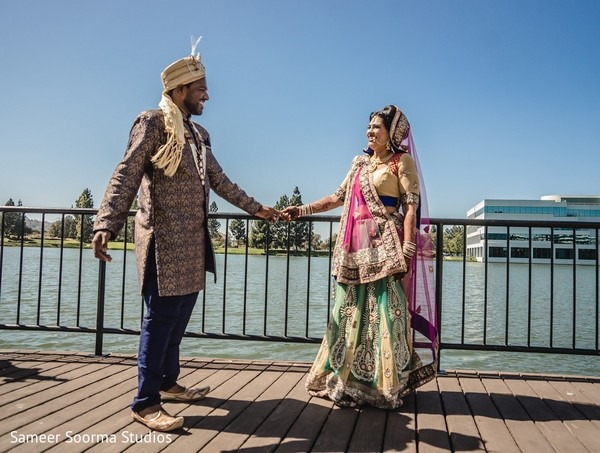 Indian bride and groom standing at the waterfront before their wedding