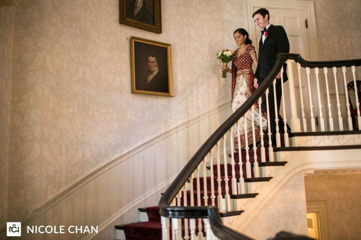Indian bride wearing a lehenga with her groom walking down stairs