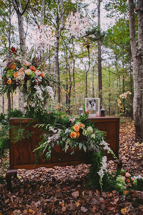 Lush outdoor setting with flower arrangements and picture frames on an old dresser.