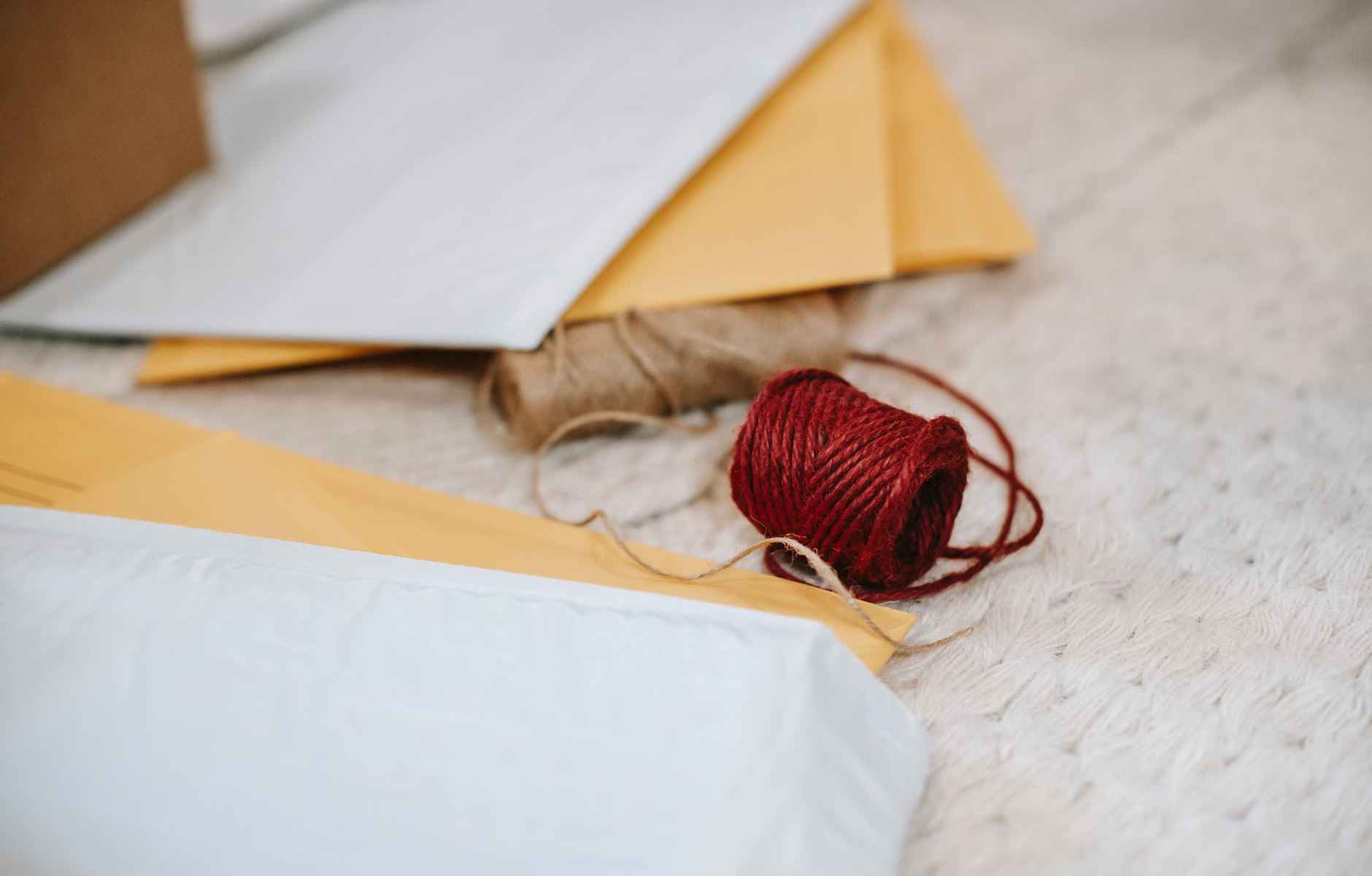woolen red and beige twine thread bobbins among envelopes