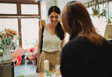 happy woman visiting floral shop and buying bouquet