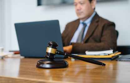 crop asian judge working on laptop in office