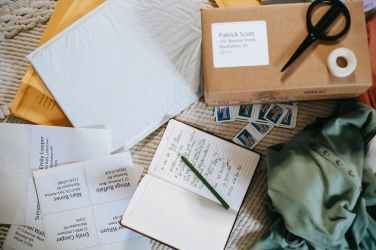 composition of opened diary carton parcel and postage stamps