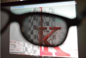 【2x3Dによる視聴の様子:裸眼では左目用2D映像,眼鏡越しには右目用映像が見えており,二重像は見えない】