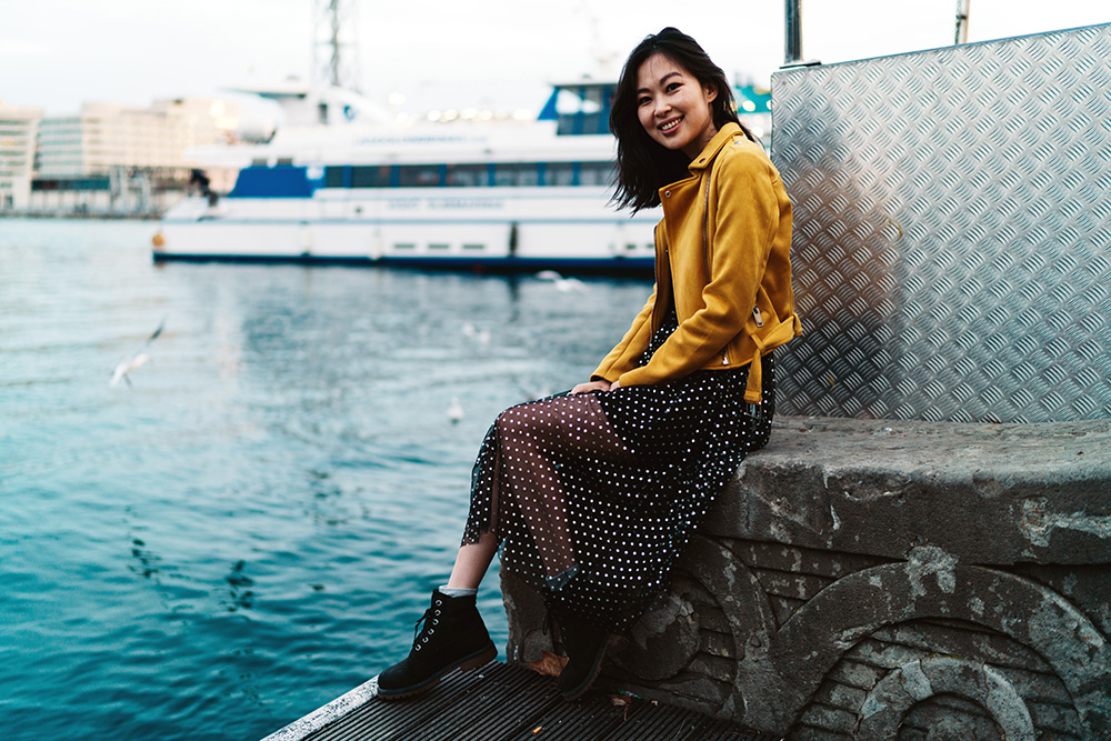 Woman sitting in the pier with her maxi dress, a yellow jacket and black ankle boots