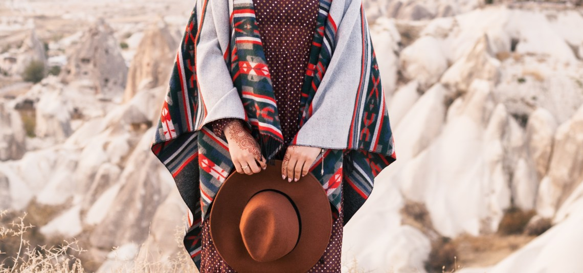 Close up of woman wearing a poncho and holding a hat.