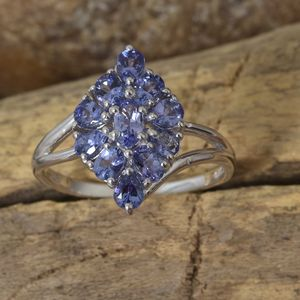 Artfully crafted tanzanite cluster ring displayed against natural wood.