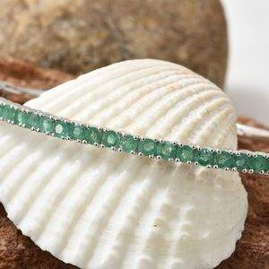 Emerald bangle displayed gracefully against sea shell.
