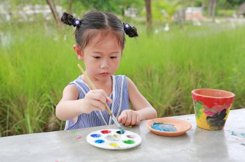 Girl painting plant pot.
