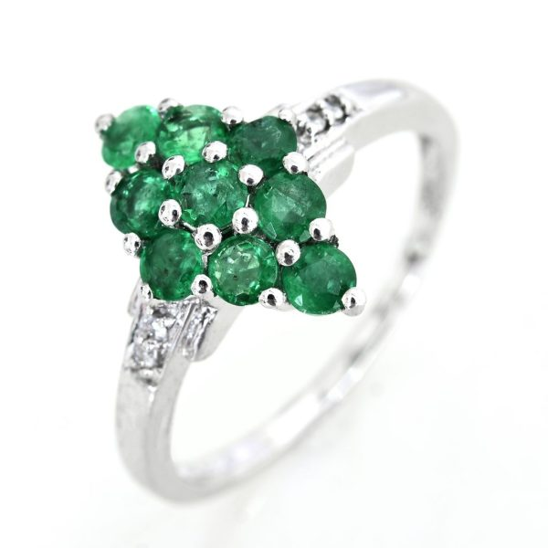 Emerald cluster ring against white background.