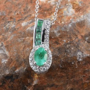 Emerald halo pendant draped over red stone display.