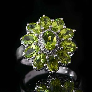 Green peridot ring on black background.