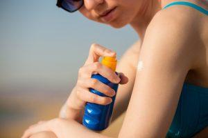A woman applies sunscreen.