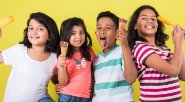 Closeup of young children eating ice cream against a yellow background