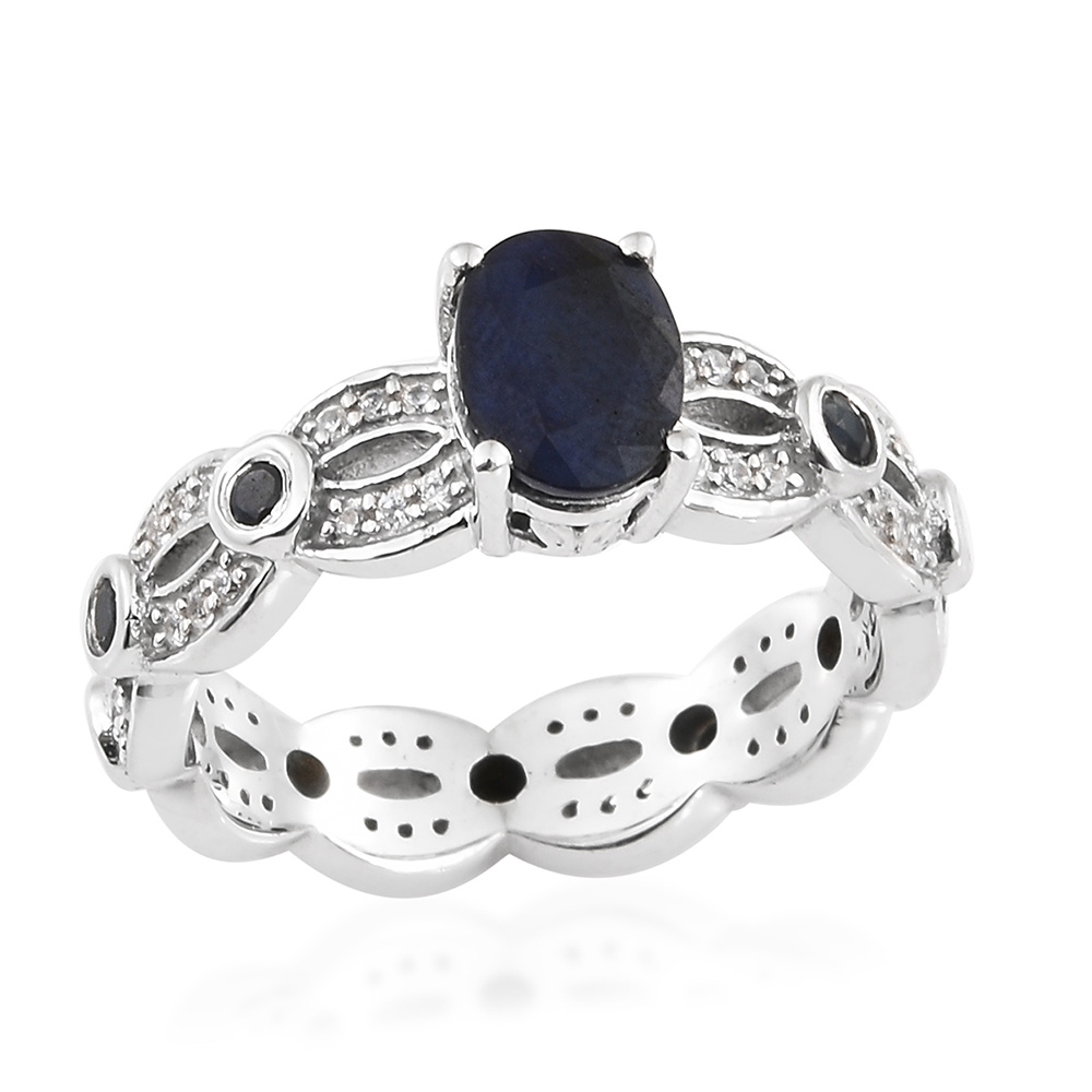 Closeup of blue sapphire ring with silver band against white background.