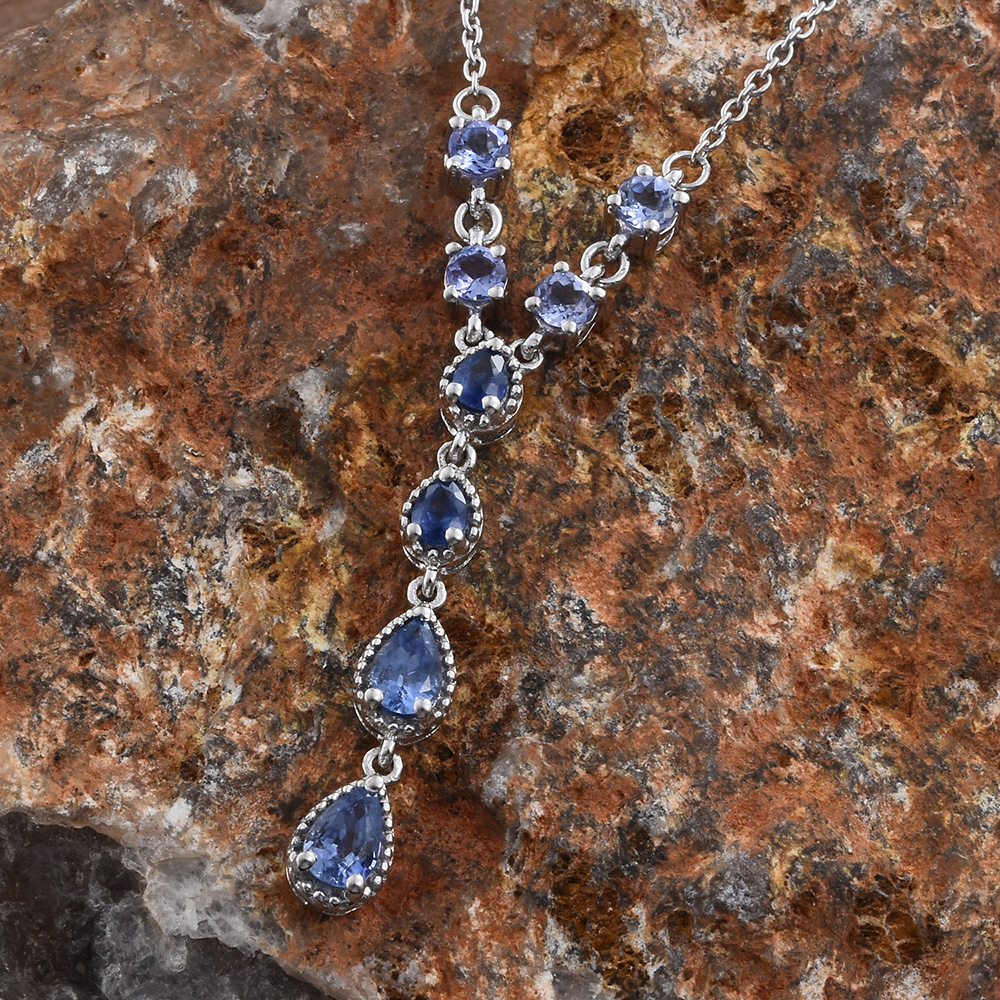 Blue sapphire necklace against brown rock.