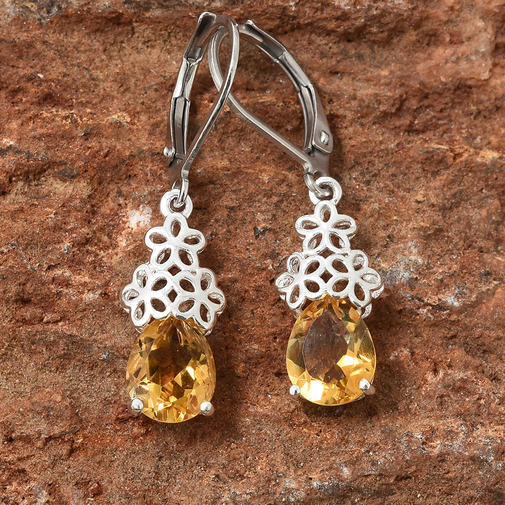 Pair of dangle citrine earrings with metal lace detail against brown marble.