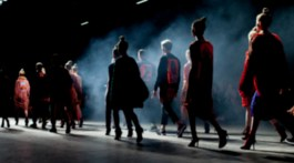 Smoky catwalk with models walking away from camera in darkened room