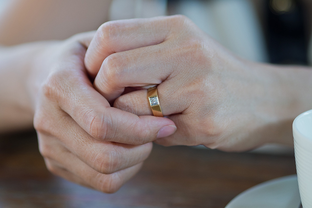 Closeup of a man fidgeting with his ring.
