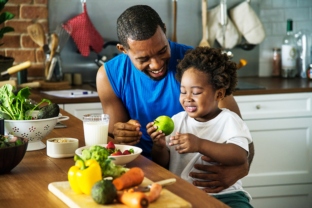 A child and his father preparing a healthy meal.