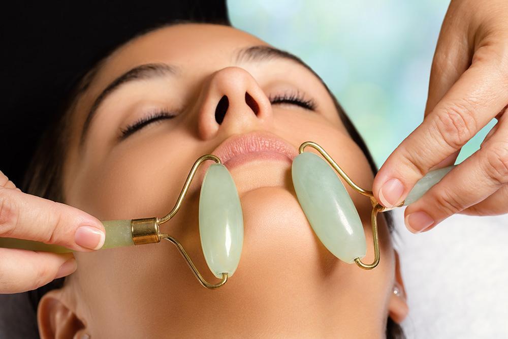 Woman undergoing jade gemstone therapy