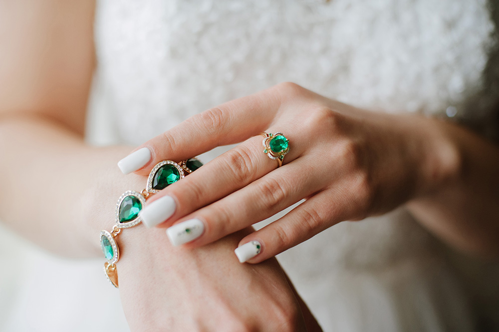 Closeup of woman with emerald ring and emerald bracelet