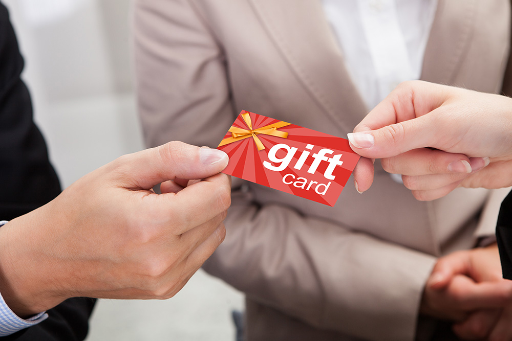 Closeup of man giving red gift card to wedding couple.