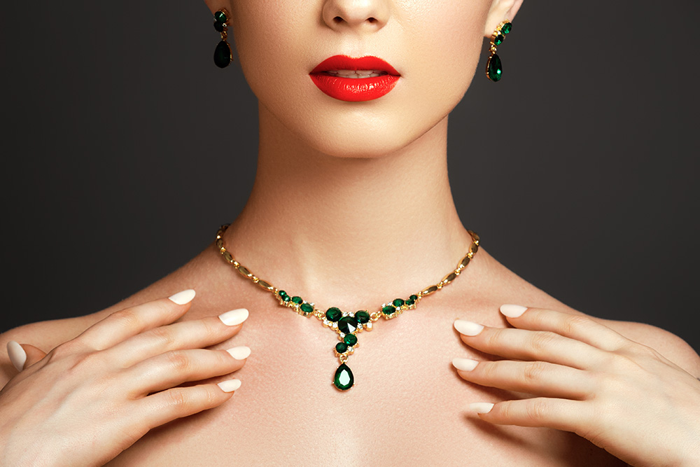 Closeup of woman wearing red lipstick posing with emerald and gold earrings and necklace