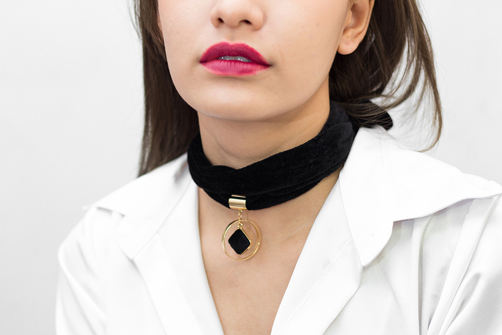 Closeup of woman wearing black bib necklace