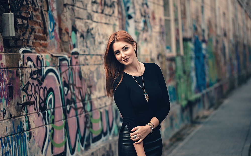 Woman wearing black tee with long pendant necklace