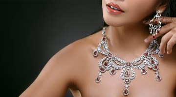 Closeup of a woman wearing earring and necklace against black background