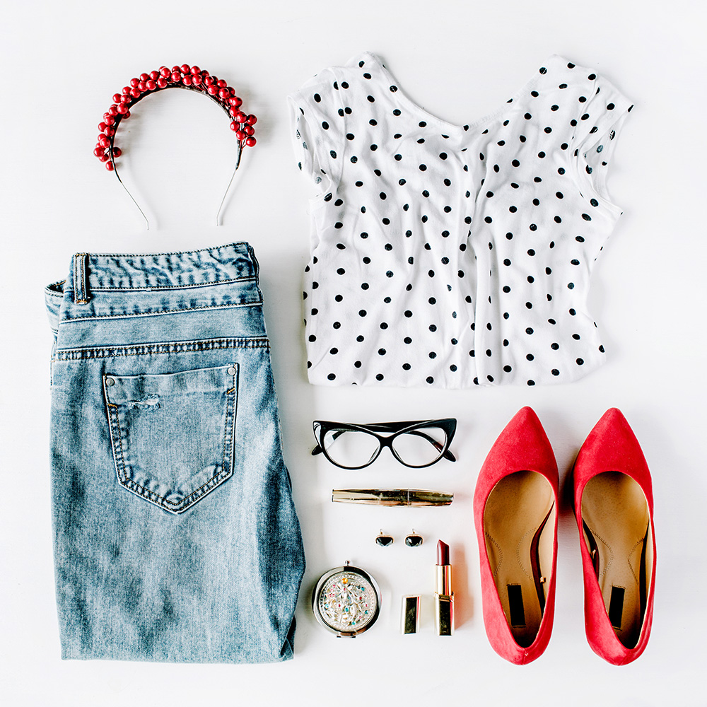 Flat lay of woman's outfit with sharp red with light denim