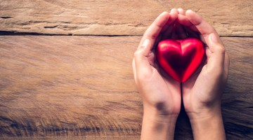 Hand holding a red metallic heart against wood background
